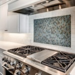 Classic white subway tile backsplash, with a handmade look blue mosaic tile accent over the range. White shaker cabinets & Carrara marble style quartz countertops complete the modern vintage look. #whitekitchen #blueaccent